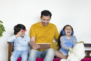 Portrait of a happy nuclear family using a tablet computer in a living room - close-up, studio, family concept