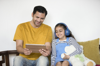 Close-up of young Indian father and kid using a digital tablet in the living room at home - family bonding, technology concept