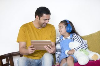 Portrait of young Indian father with daughter using a digital tablet - technology concept