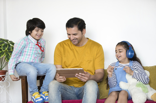 Happy Indian family - father and children.  Daughter and son with tablet computer at home - technology concept
