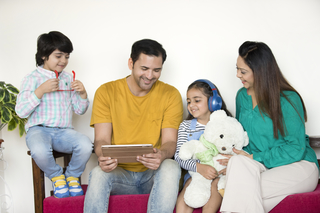 Portrait of Indian healthy family sitting together and enjoying - gadgets, technology, family concept
