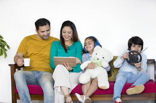 Happy Indian family using digital devices while sitting on the sofa at home - technology concept