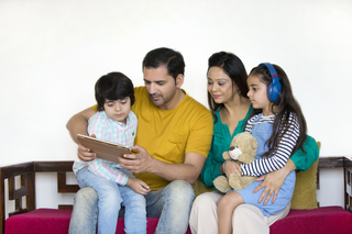 Happy multi-ethnic family using a digital tablet while sitting on the sofa at home - nuclear family concept