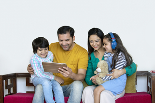Smart Indian family sitting together on sofa -listening to music and watching video on the tablet - technology concept