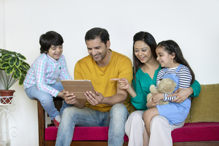 Portrait of a healthy family with two children - looking at something funny in their tablet