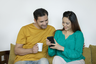 Close-up of an attractive wealthy successful couple holding each other and watching their mobile screen