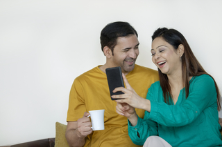 Cheerful young husband and beautiful wife having coffee and watching a funny video on the mobile phone