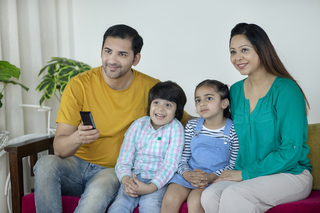 Beautiful young parents and their children are watching TV and smiling while sitting on the sofa at home