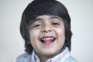 Close-up portrait of a charming child boy laughing - posing towards the camera. Studio, isolated