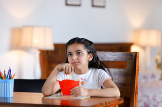 Cute little Indian child girl sitting and thinking while eating - isolated image