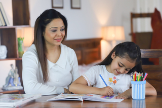 Happy young mother looking at her child, daughter doing homework - motherhood, education concept