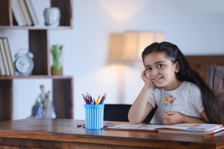 Portrait of a charming child girl sitting while posing towards camera - childhood, closeup image