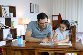 Young Indian father helping charming daughter while studying - education concept