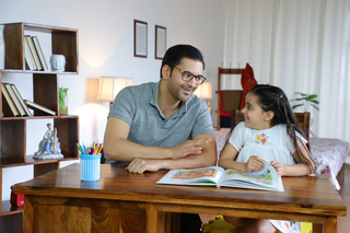 Happy young father and beautiful little daughter looking at each other while studying - parenthood, family emotions