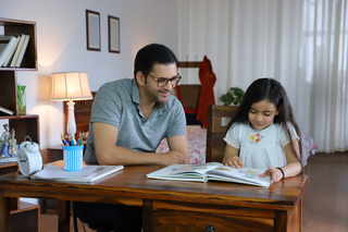 Portrait of smiling father helping cute daughter reading a storybook - Childhood, Parenting Concept