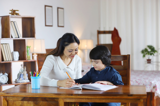 Portrait of a beautiful mother helping son in drawing / study- education concept, family emotions