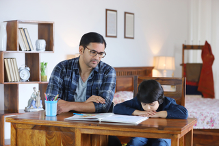 Portrait of Indian family sitting together, father advising son for studies - Education concept