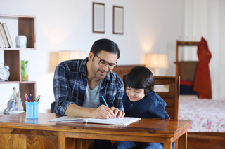 Young Indian father helping son to do homework at home - education concept, family, childhood