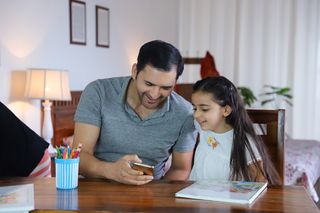 Image of an Indian father and daughter watching a video in mobile phone / smartphone - Parenting, Love, Care