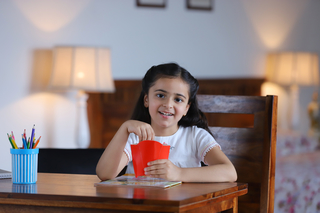 Little happy girl eating french fries and enjoying the food at home - Childhood, Study Room