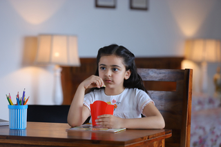 Thoughtful little Indian girl thinking while eating french fries - isolated, study room