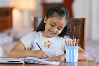 Cute little schoolgirl studying at home - isolated, childhood, education concept