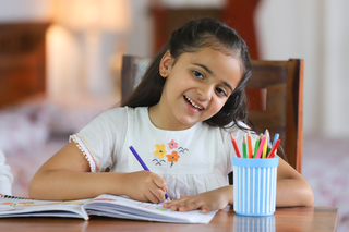 A 5-year-old little Indian girl drawing with pencils at home - education concept