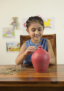 Indian child girl putting coins in the piggy bank for saving money - savings concept