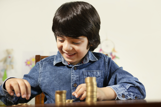 Young smart boy counting his coins/savings to buy dream toys - Saving concept