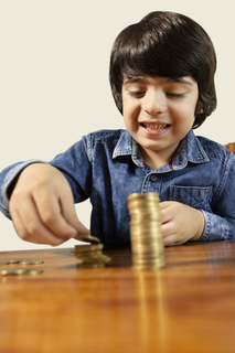 Little boy playing with coins making stacks and learning financial responsibility and planning - savings concept