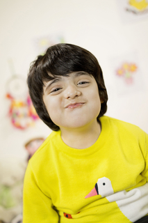 Closeup image of a cheerful kid of school age having fun - posing isolated