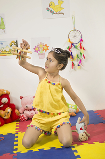 Pretty little Indian girl wearing a crown is playing with a toy plane