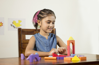 Cute little Indian girl child playing with toys at home - preschooler
