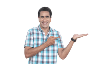 A smart Indian man in checkered shirt posing  and pointing on the right side - White background