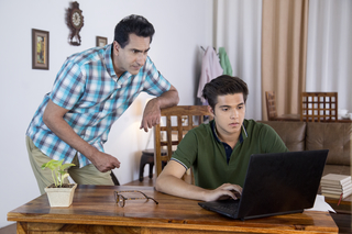 Father and Son - Teenager boy using laptop and father looking over - Young family
