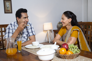Smiling Indian husband and wife on the dinner table - Wife wearing saree, enjoying dinner meal