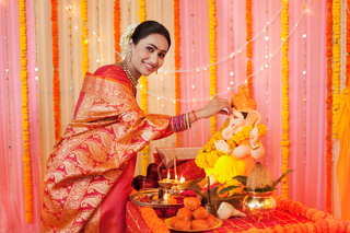 Portrait of an Indian woman putting tilak on Lord Ganpati's idol - Festival celebration