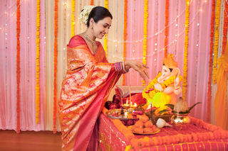 Happy Indian woman offering flowers on Lord Ganesh idol: Indian festival Ganesh Chaturthi
