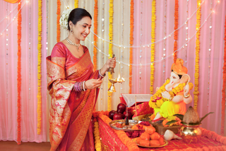 Indian woman offering aarti (pooja / puja) on Ganesh festival: Ganesh Chaturthi