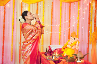Image of an Indian woman in silk saree blowing shankh or a conch shell on festival puja/pooja: Diwali/Ganesh Chaturthi/Guru Purnima