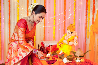 Portrait of a young happy woman doing Ganesh puja/pooja on Ganesh Chaturthi: Indian festival culture