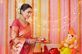 Happy Indian woman performing Ganesh aarti on Ganesh Chaturthi: Festival celebration
