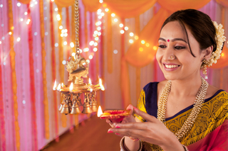Beautiful young Indian female holding a diya and lighting up hanging brass diyas on Diwali festival