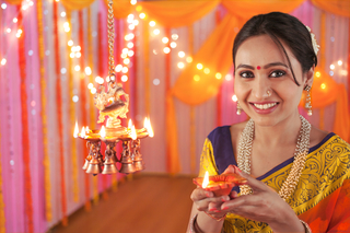 Traditional woman holding Diya or terracotta oil lamp on diwali festival - Happy Woman