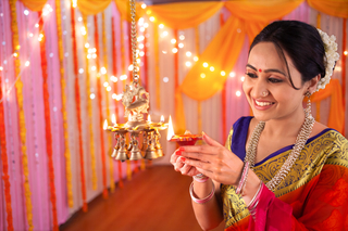 Indian beautiful woman holding a diya or terracotta oil lamp and lighting diyas - Diwali Decoration
