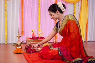 Young traditional Indian woman preparing for puja rituals using rose flowers and ladoo sweets