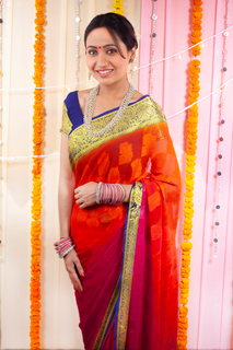 Beautiful Indian woman smiling and posing in front of the camera in traditional saree jewelry