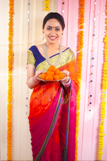 Beautiful young Indian woman holding a plate full of Indian sweets - ladoo. Festival feast / Prasad