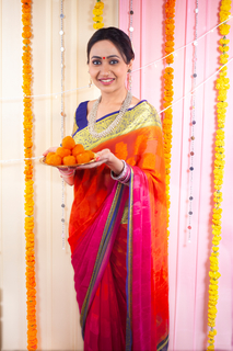 Woman holding a plate of ladoo sweets - Diwali festival in India