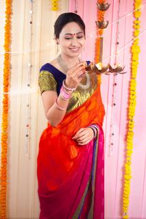 Pretty Indian woman lighting diyas on diwali festival - Diwali Lights
